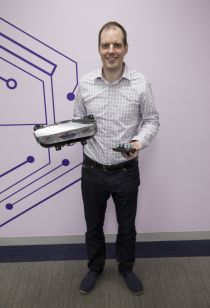 NYU Tandon Professor Justin Cappos, one of the leaders of the Uptane project, holds two of the automotive components that are vulnerable when automakers or mechanics update their software for recalls or performance modifications