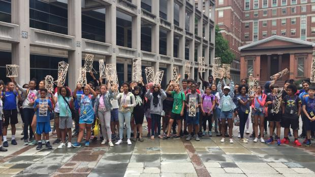 Summer of STEM students pose with their projects outside of NYU Tandon's Pfizer Auditorium.