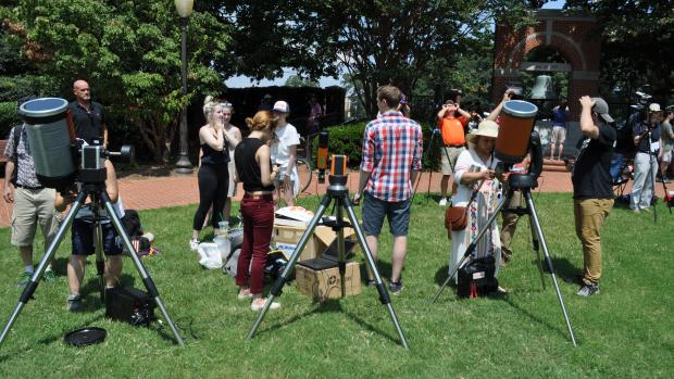 students with telescopes on a lawn
