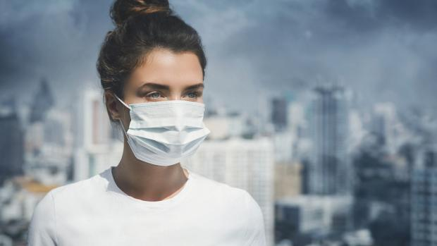 woman wearing mask in city smog