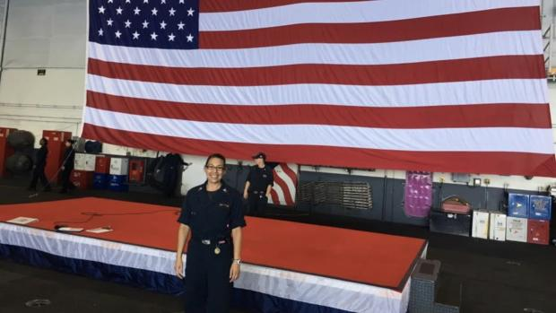 Jessica Espinoza in her uniform in front of a large American flag.