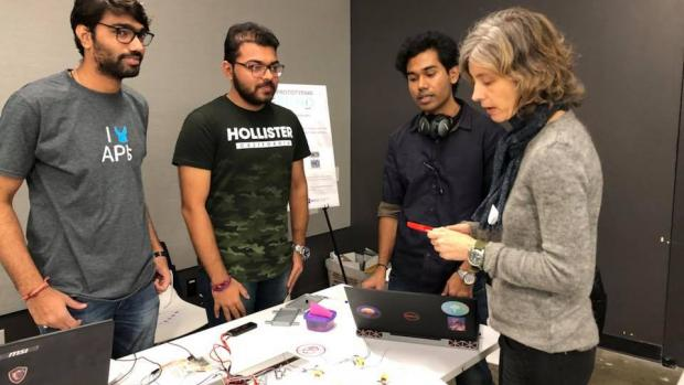 Swapnesh Wani, Purva Patel, and Supreeth Kumar demonstrate their flying mobile case to Associate Professor Anne-Laure Fayard at the Prototyping Fund Showcase