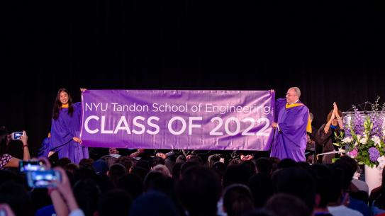 student and alumnus holding Class of 2022 banner
