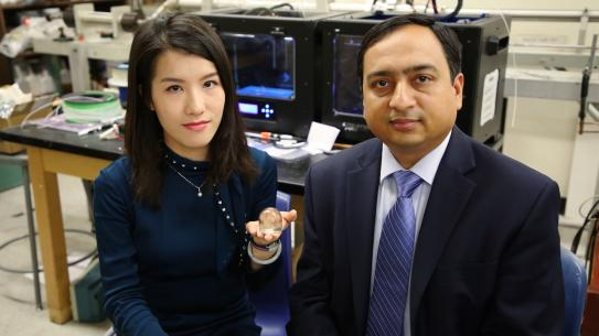 Fei Chen holding a 3D printed item next to Professor Gupta
