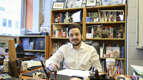 Maurizio Porfiri in his office with bookshelves in background