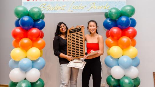 2 women students holding award