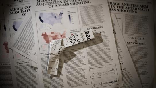 newspaper folded to look like a gun