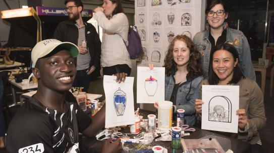 group of students holding up drawings at IDM showcase