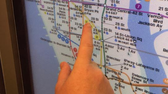 finger pointing at subway map touchscreen