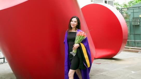 Asian student in graduation gown