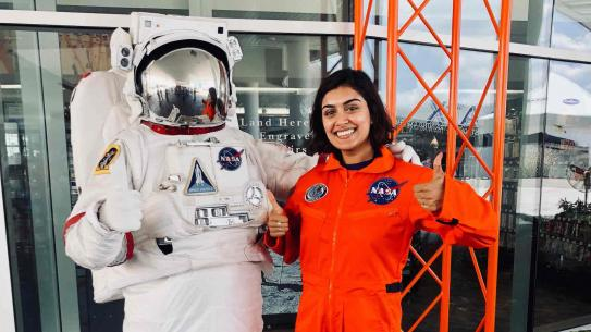 alum Tanya Gupta next to a space suit