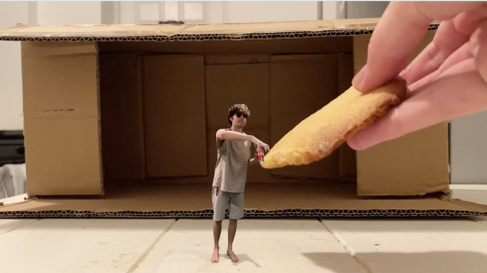a still from a video showing a miniature student accepting a huge cookie