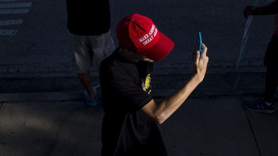 man wearing MAGA hat staring at phone