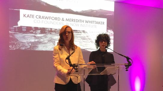 Kate Crawford and Meredith Whittaker speaking at a podium