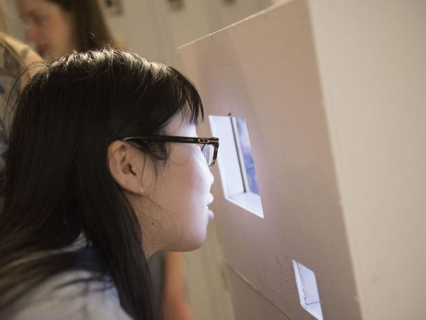 student peering through project window