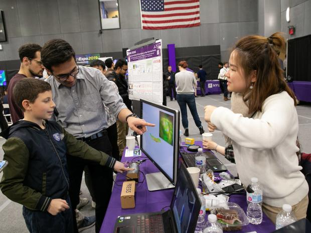 boy looks at research expo exhibit