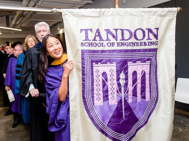 student holding Tandon banner