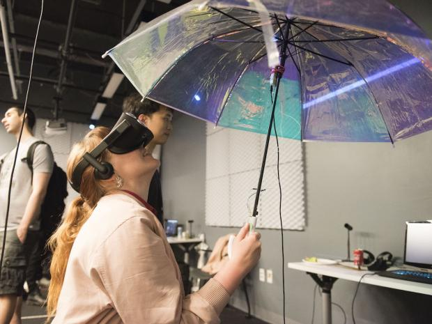 student wearing VR headset looking up at umbrella