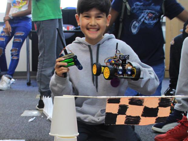 student holding up a circuit car