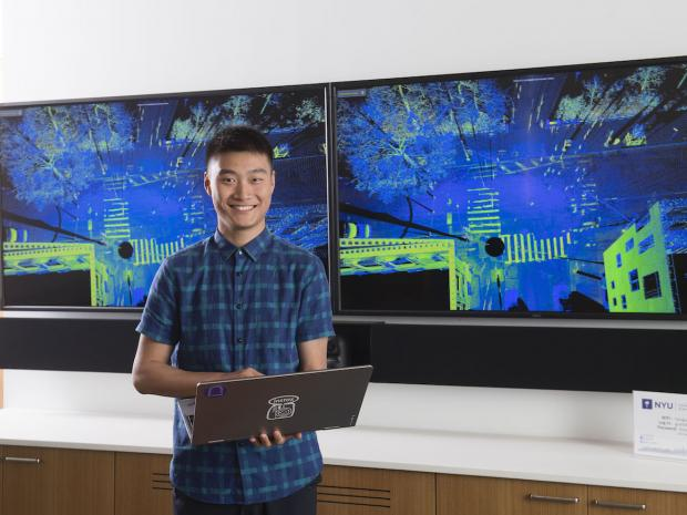 smiling asian male student holding laptop in front of large digital screen