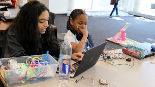 Two Science of Smart Cities students program an Arduino board.