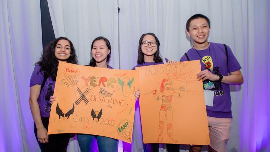 Orientation leaders show off the superhero-themed posters they created for their orientation groups