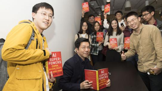 Kai-Fu Lee with group of students all holding his book