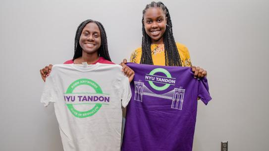 Two female students of color holding NYU Tandon tshirts