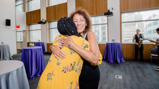 Dean Farrington hugging person at students of color reception