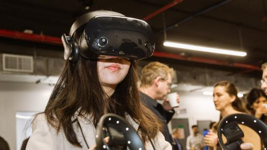female student wearing a VR headset and holding controllers