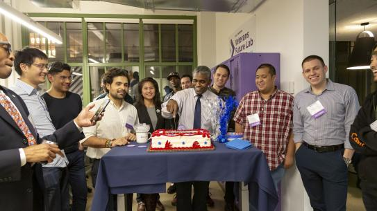 Alumni and members of the Veterans Future Lab look on as Director James Hendon cuts the cake