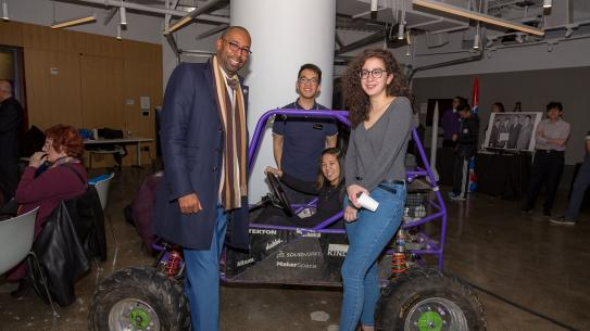 Students in NYU Tandon's Motorsports team display their vehicle to an alumnus