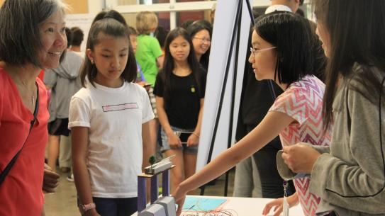 students discuss their expo project with a parent