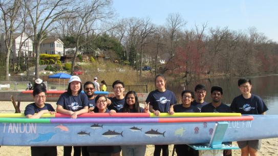 Students outdoors with their blue canoe at the competition