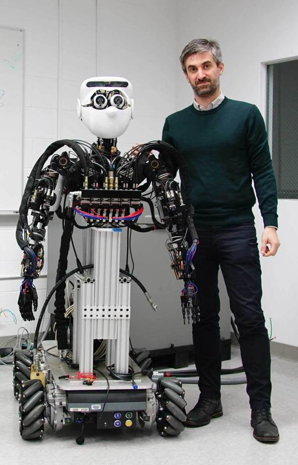 Man standing next to robot