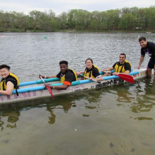 Students in a canoe rowing in a lake