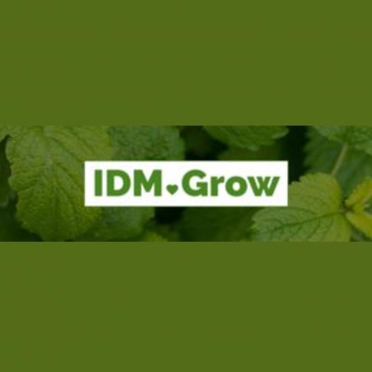 "A backdrop of green leaves with ""IDM grow"" overlaid on it."