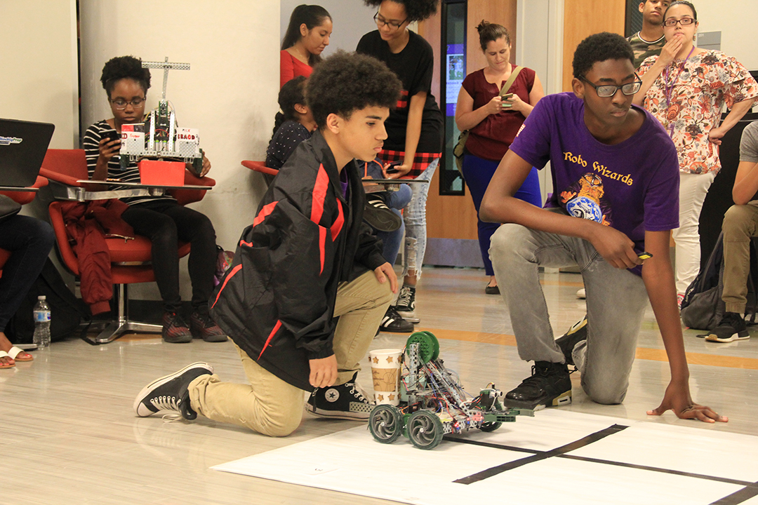 ITEST students watching their robots move in a competition
