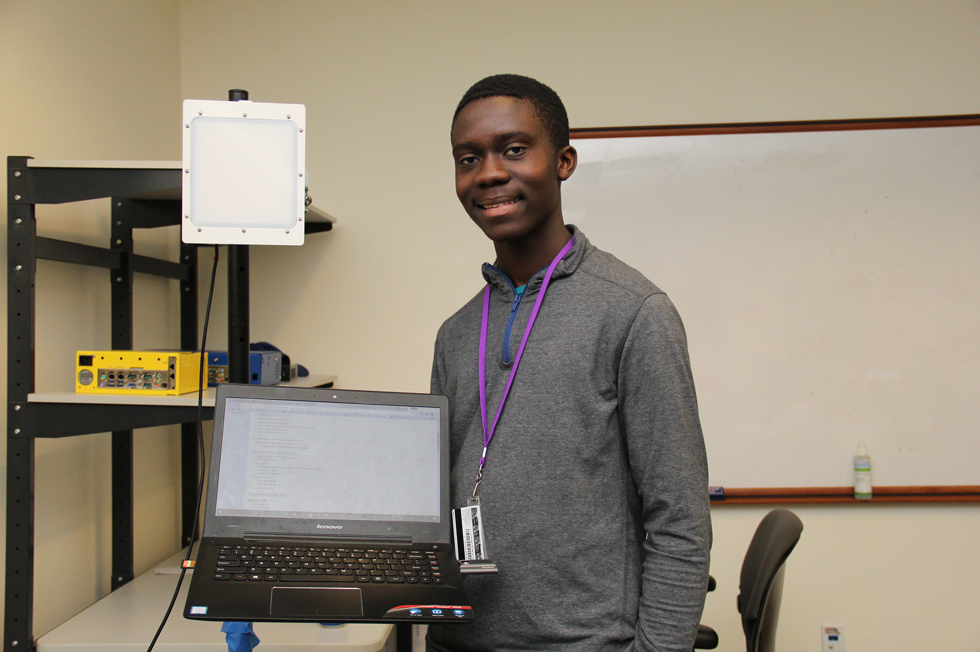 student holding up a laptop