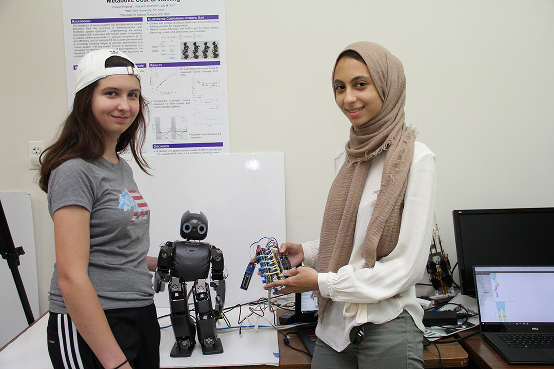 two students holding up a robot