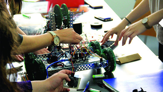 student hands working on robot